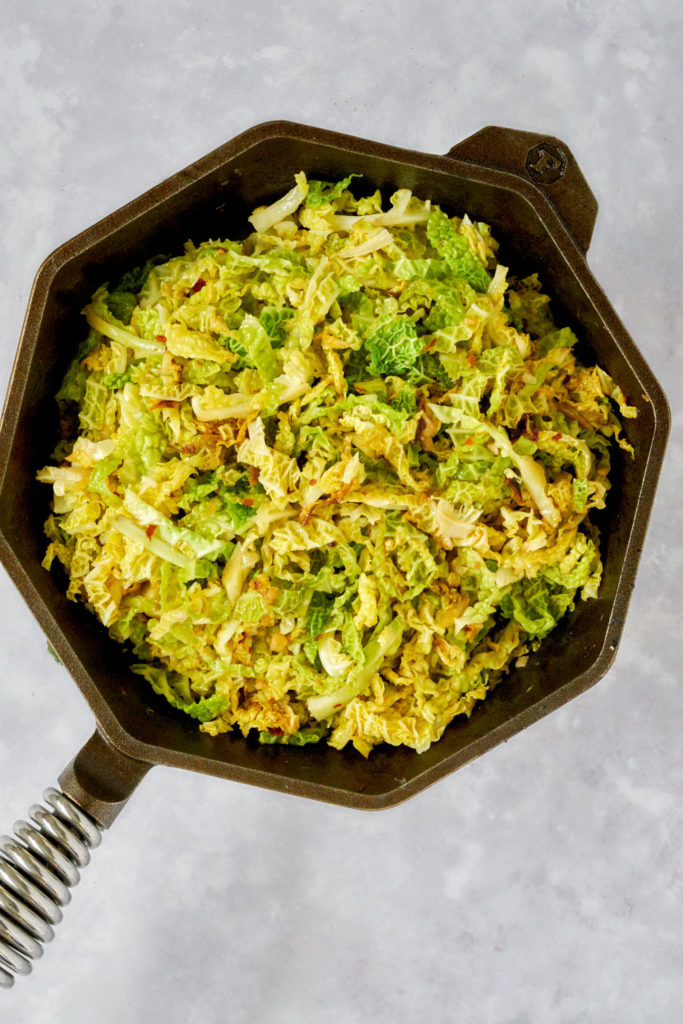 Cooked cabbage in a cast iron pan.
