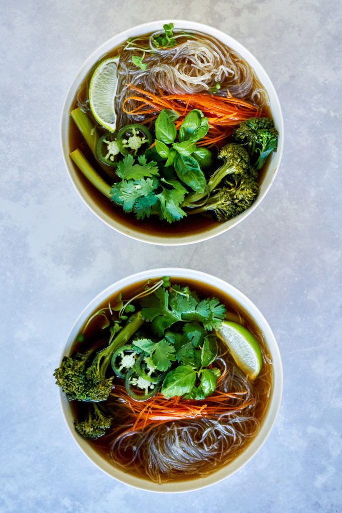 Two bowls of noodle soup with vegetables and herbs.