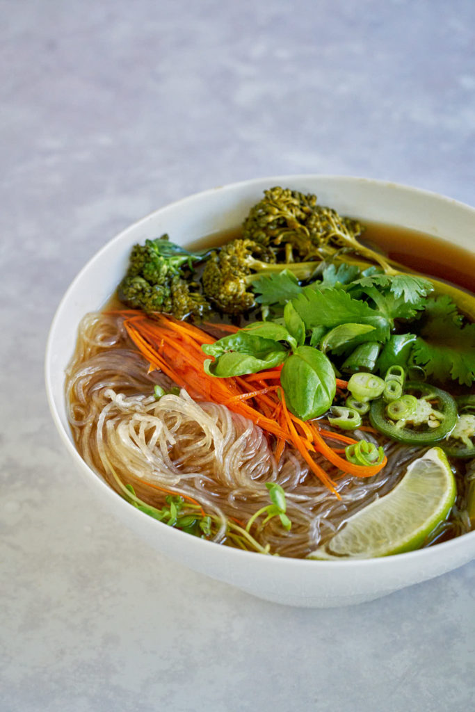 One bowl of noodles soup with vegetables and herbs.