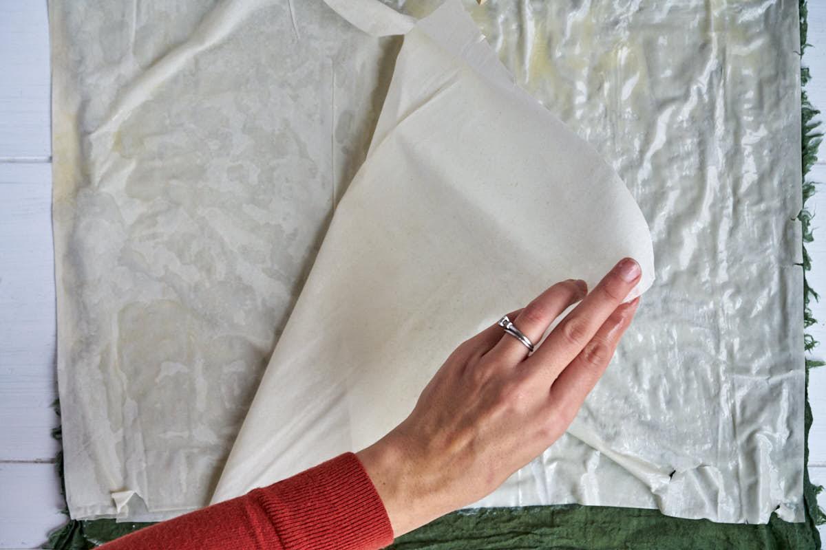 Layering sheets of phyllo dough.