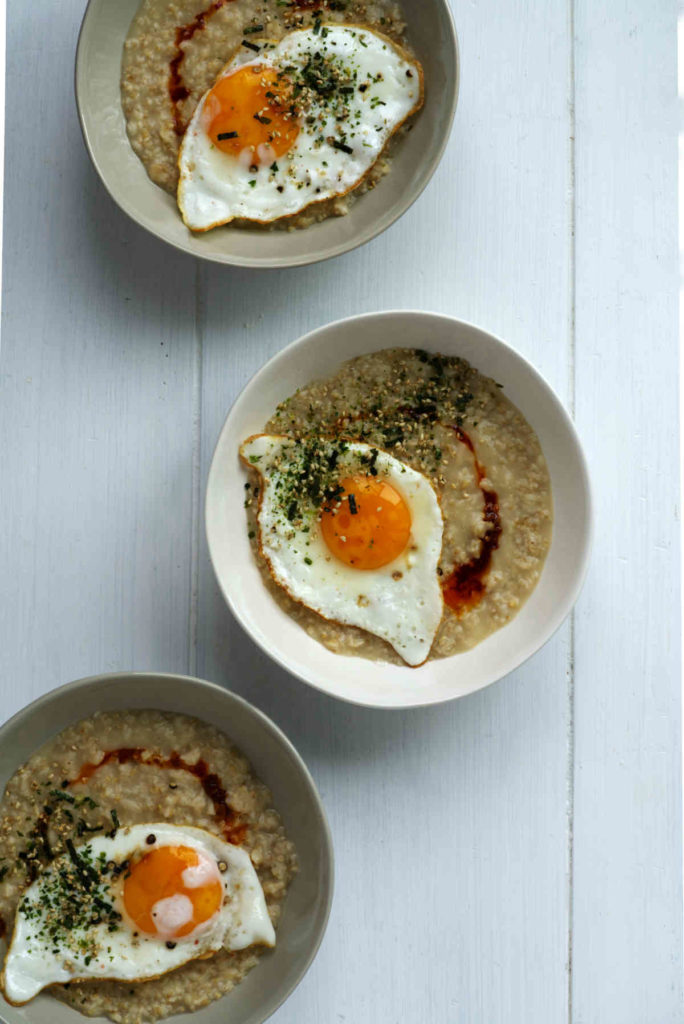 Three bowls of oatmeal with eggs.