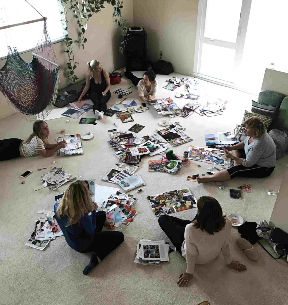 People on the floor of a room with magazines and crafts.