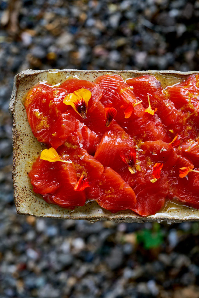 Salmon crudo on a ceramic platter decorated with nasturtium petals.
