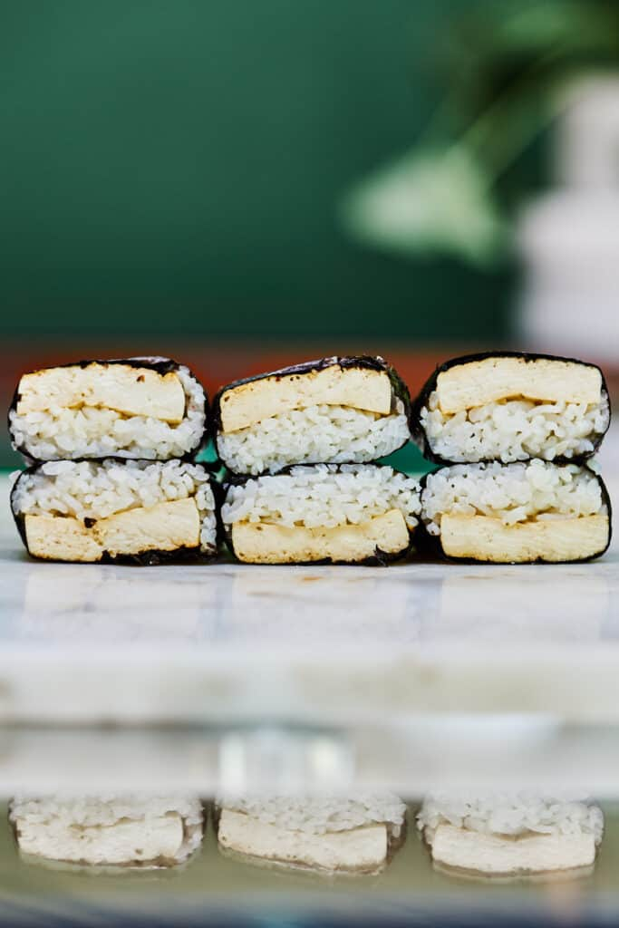 Six tofu musubi stacked on a white countertop.