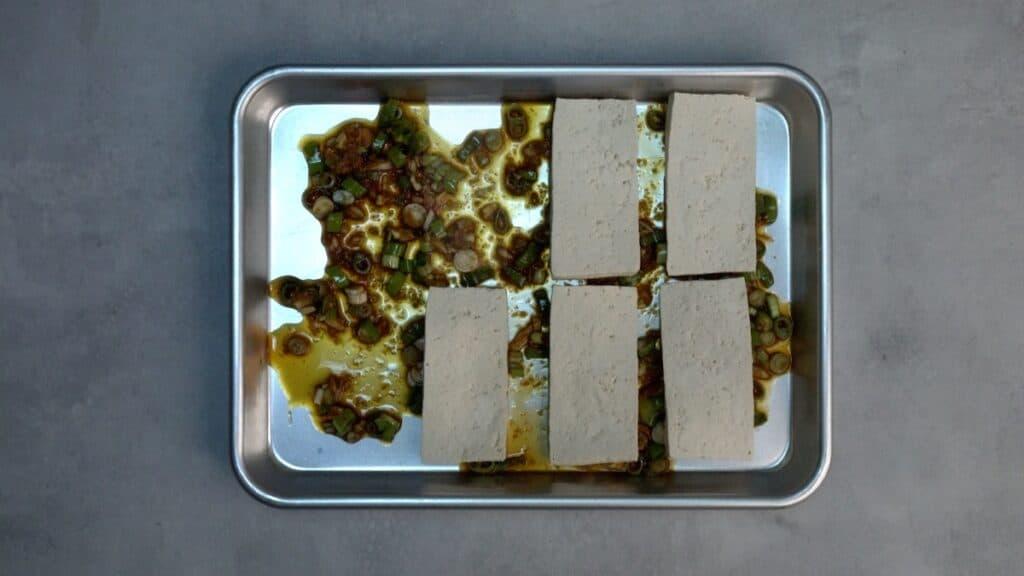 Tofu and marinade in a sheet pan.
