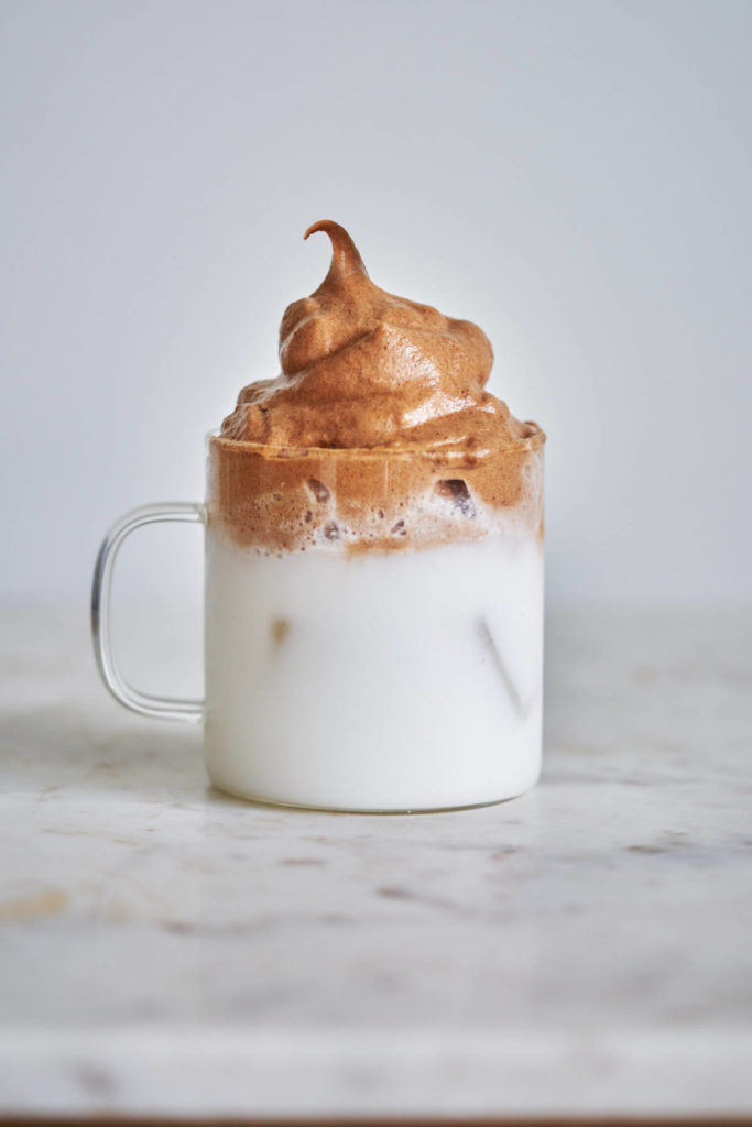 Whipped chocolate over milk in a clear glass cup.