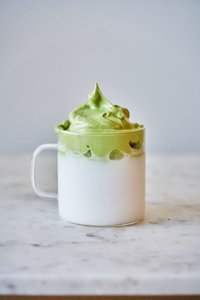 Cup filled half way with coconut milk and topped with matcha foam.