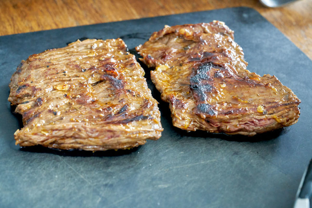 Cooked skirt steak on a black cutting board.