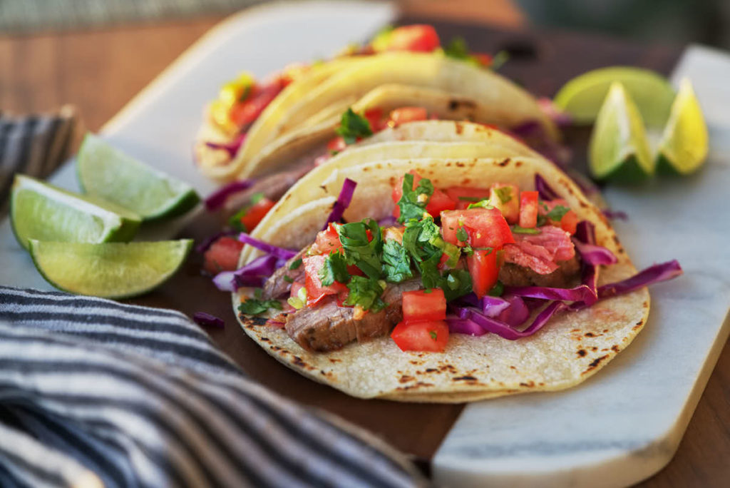 Open faced steak taco with tomatoes and cabbage.