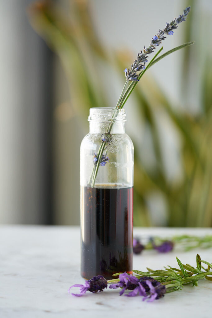 Lavender simple syrup in a slender jar with a few stems of lavender.