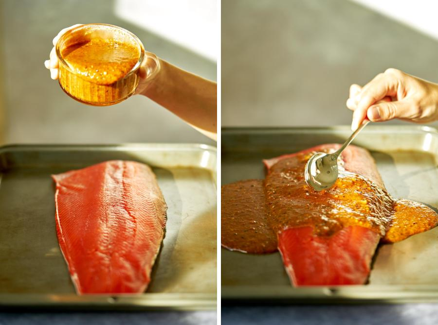 Pouring marinade over salmon and spreading it with a spoon.