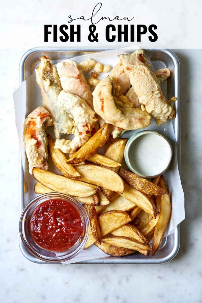 Fried fish on a baking sheet with fries and ketchup.