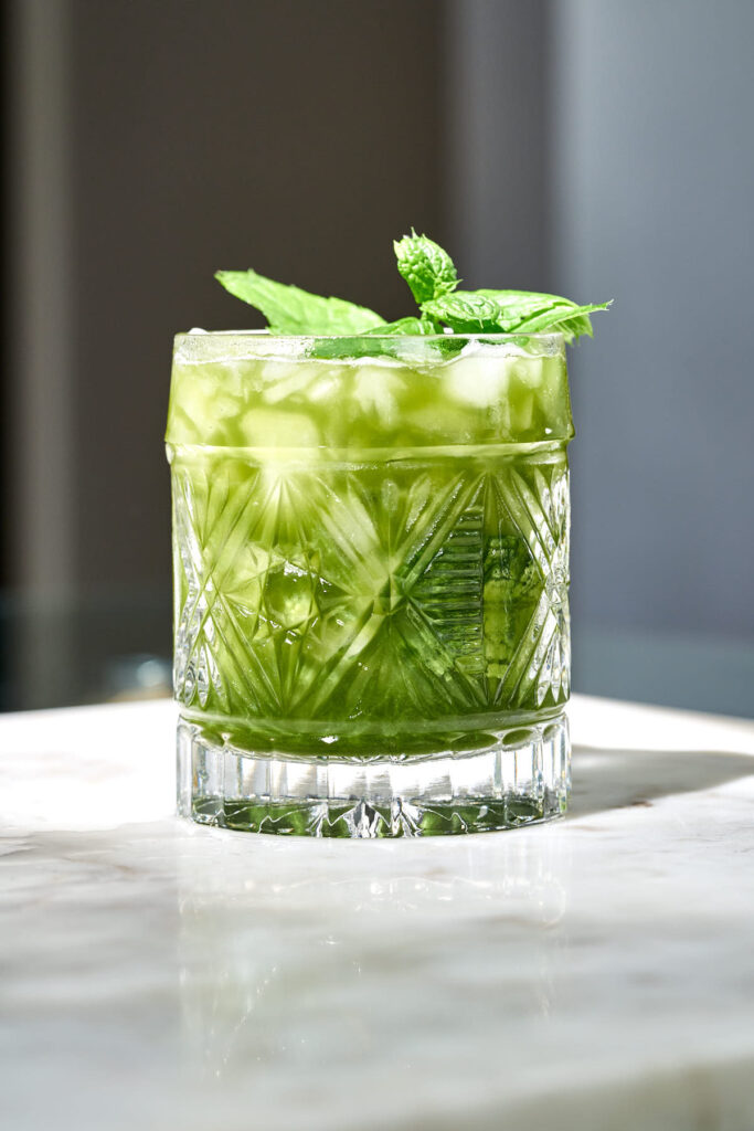 A green tea cocktail fulled with crushed ice and garnished with mint.