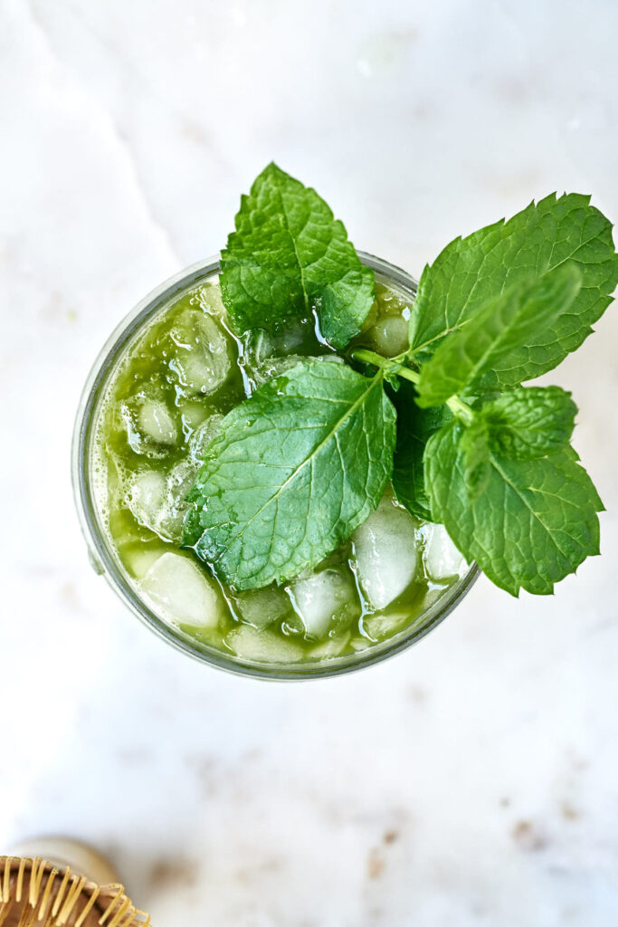 Top view of a matcha cocktail filled with crushed ice and garnished with a sprig of mint.
