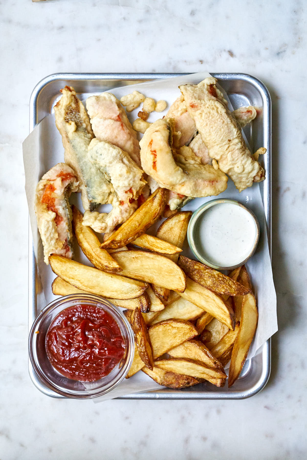 Fish and chips on a tray with tartar and ketchup.