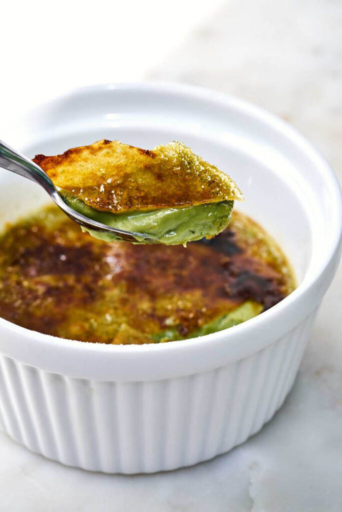 Spoon scooping out the perfect bite of matcha creme brulee.
