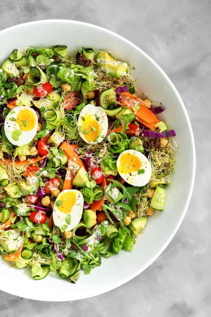 Top view of a meal salad with jammy eggs and poppyseed dressing.