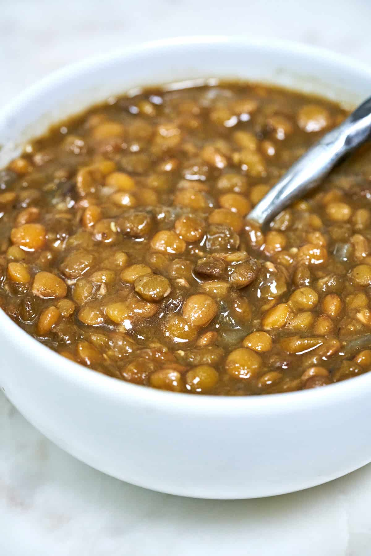 Bowl of lentils with a spoon.