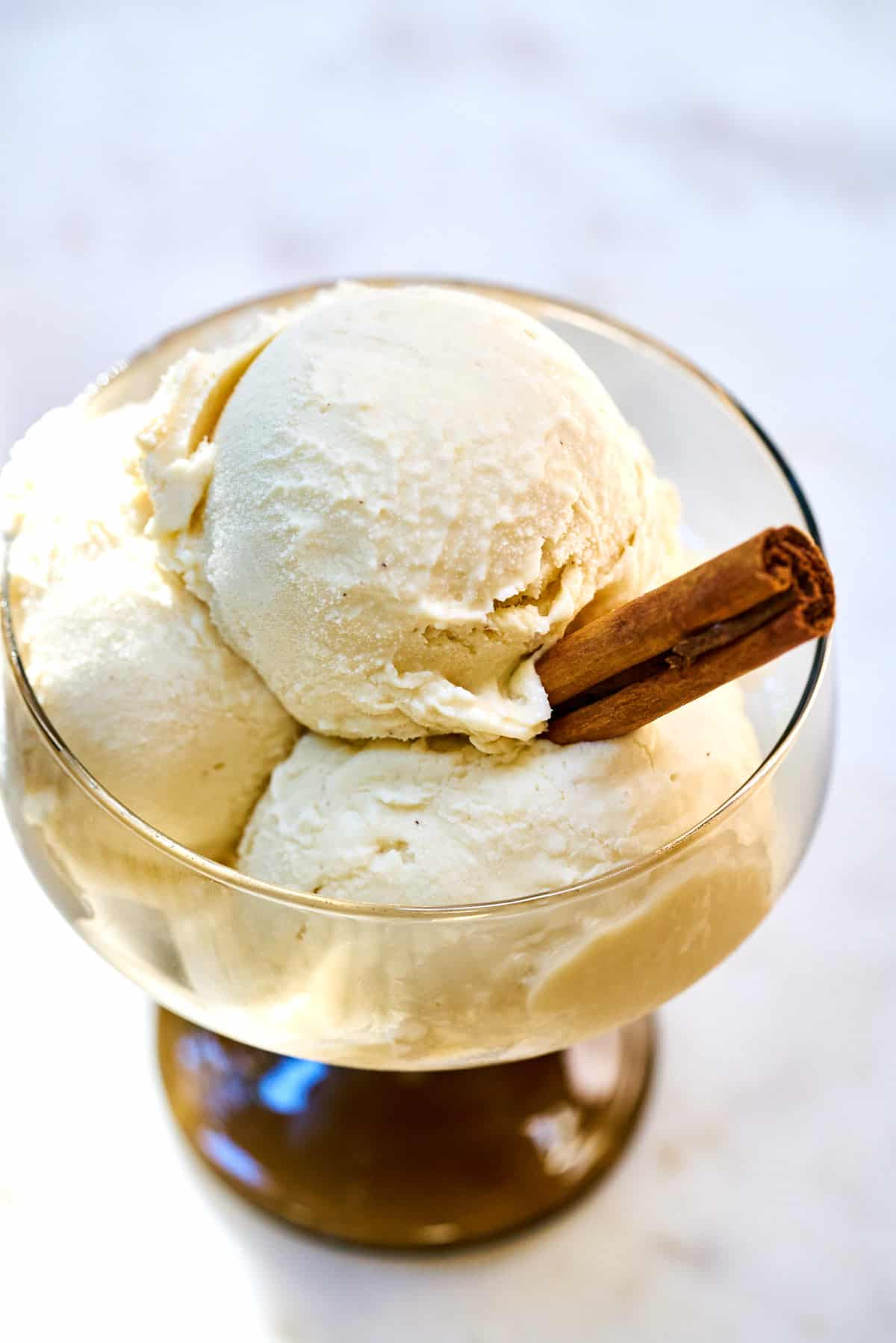 Three scoops of ice cream in a pedestal glass with a stick of cinnamon.
