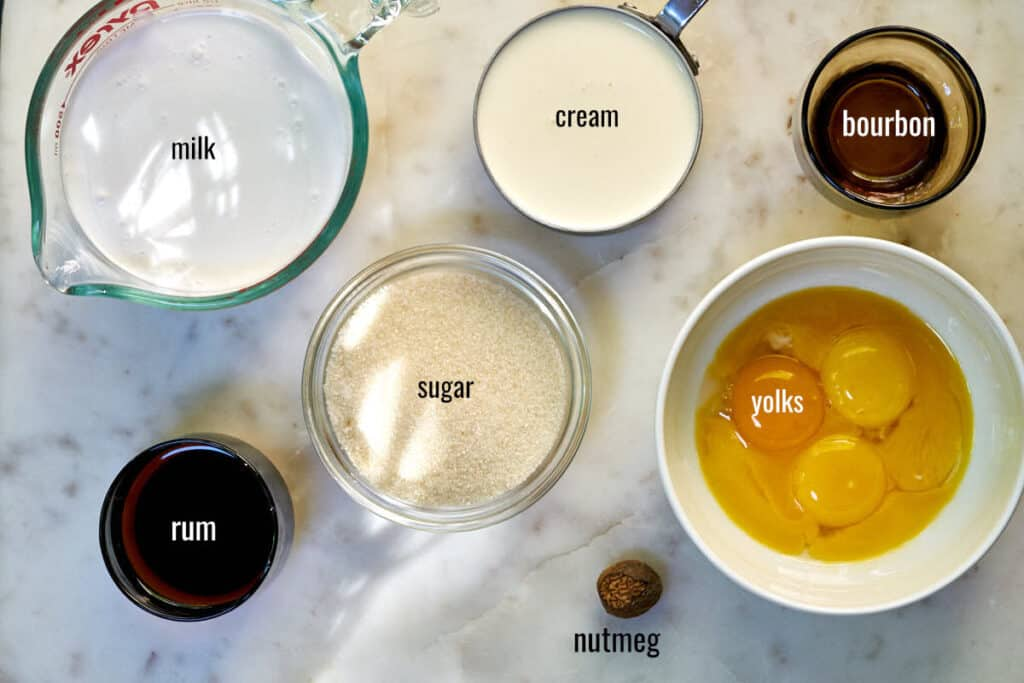 Labeled ingredients for eggnog ice cream including milk, cream, yolks, and nutmeg.