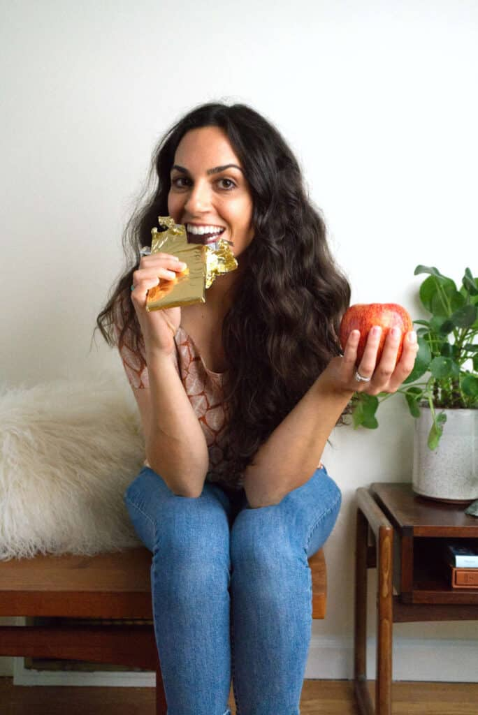 Woman eating chocolate and holding an apple.