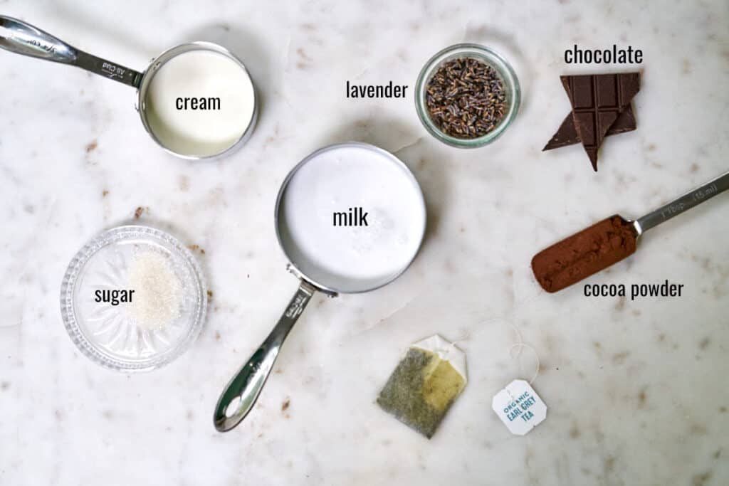 Ingredients for Earl Grey hot chocolate and lavender whipped cream on a white countertop.
