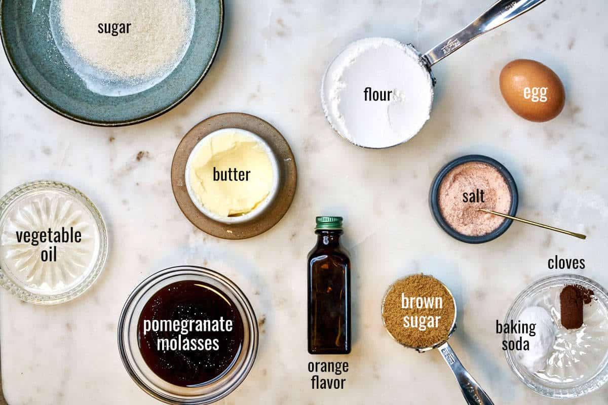 Ingredients for cookies on a white countertop including pomegranate molasses, orange flavor, and cloves.