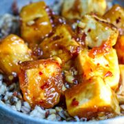 Sticky tofu in a ceramic bowl with brown rice.