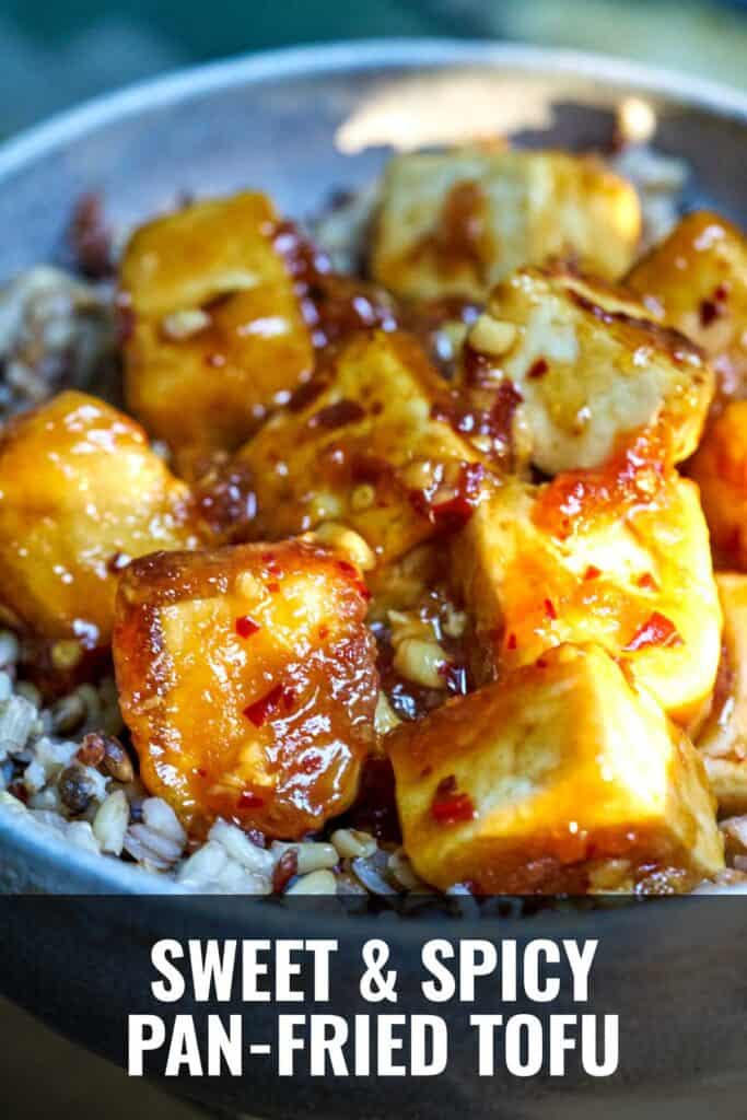 Tofu cubes covered in sticky sauce over rice.