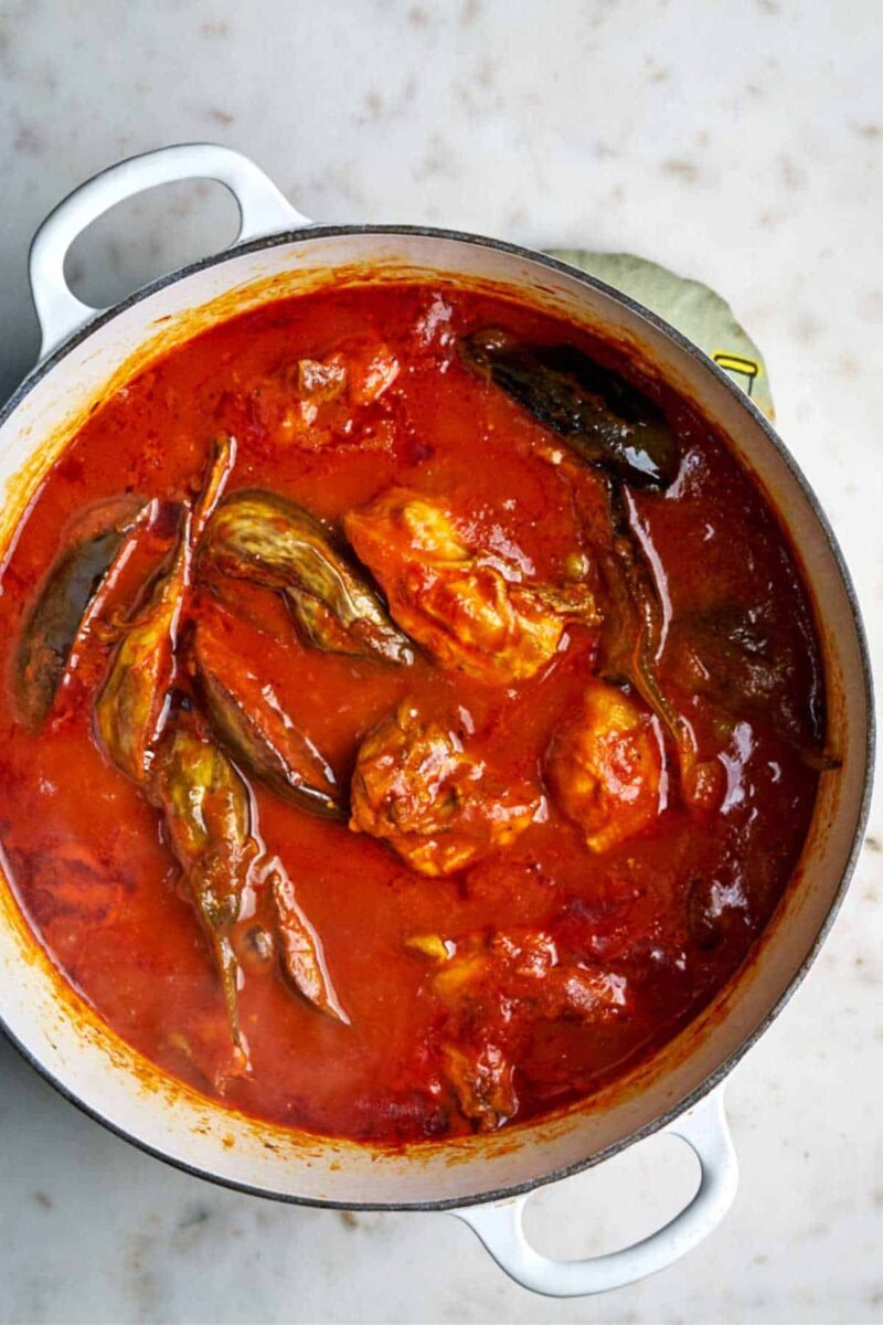 Top view of cooked eggplant stew with chicken in red sauce.