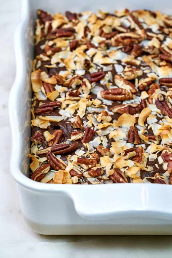 Cake in a white baking dish covered in pecans and coconut after baking.