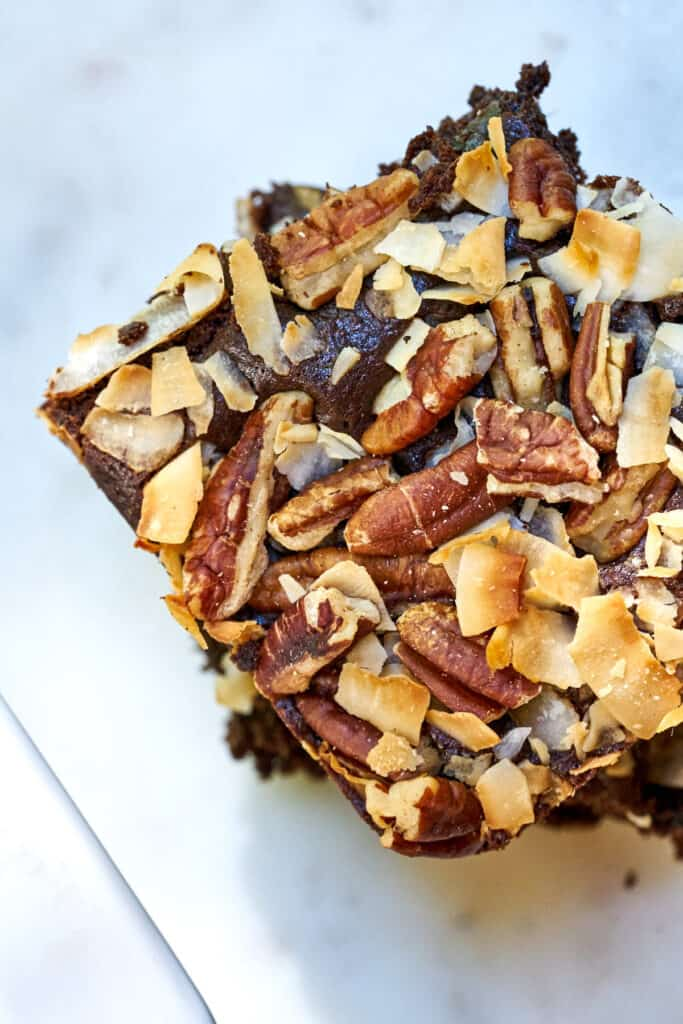Top view of two slices of cake covered in coconut and pecans.