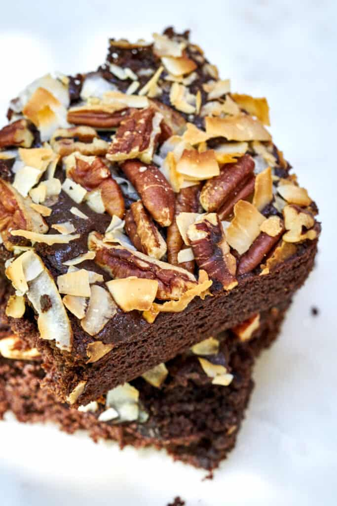 Two pieces of chocolate cake with coconut and nuts stacked on top of each other.