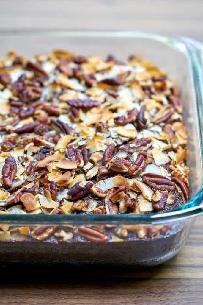 Cake in a glass baking dish covered in pecans and coconut after baking.