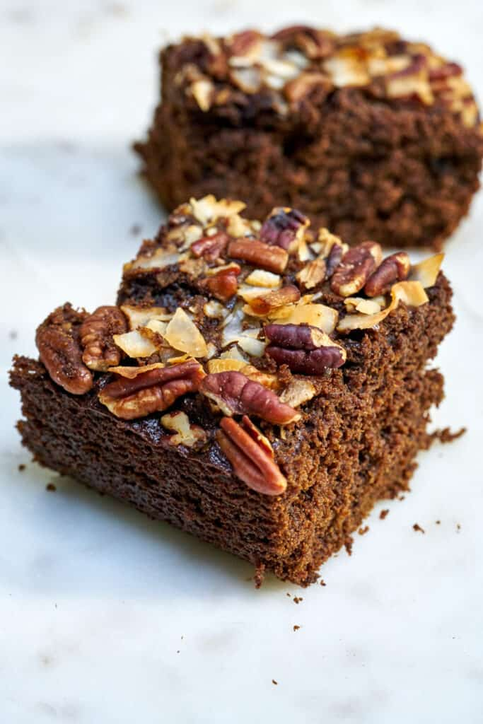 Two slices of brown cake topped with nuts and coconut.