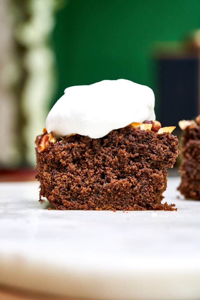 Front view of one piece of cake topped with whipped cream on a white table with green background.