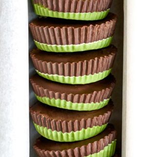 Stack of peanut butter cups that have green bottoms and chocolate tops.