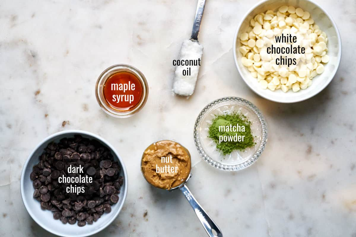 Ingredients on a white countertop including white and dark chocolate chips.