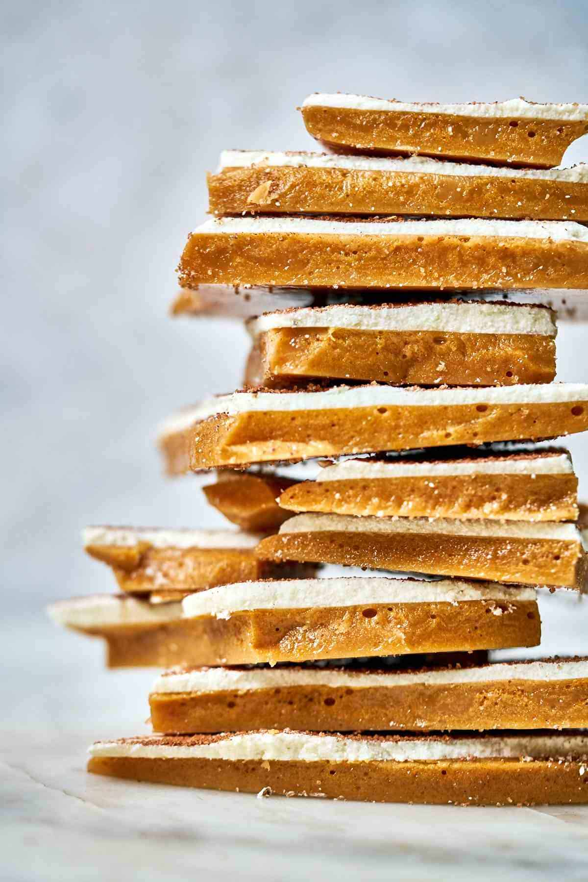 Stack of toffee with white chocolate and a white background.