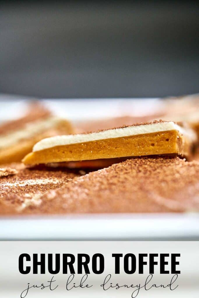 Close up of a piece of toffee on a sheet pan filled with toffee.