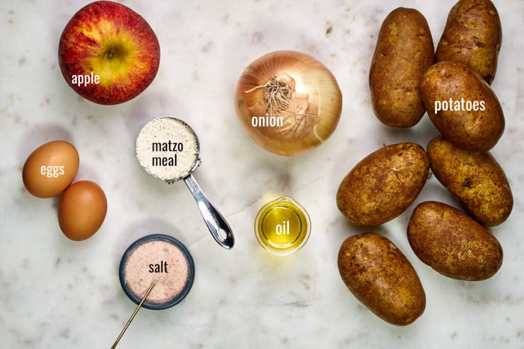 Ingredients for latkes including potatoes, onion, apple, eggs, matzo meal, oil, and salt.