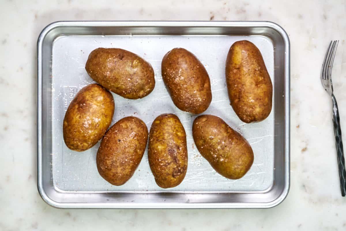 Seven potatoes on a quarter baking sheet next to a fork.