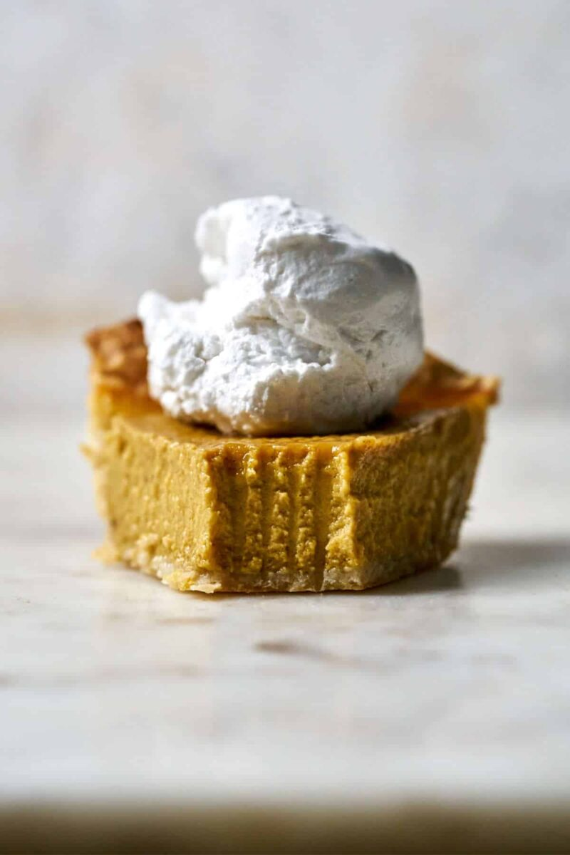 Front view of a slice of pumpkin pie with whipped cream on top.