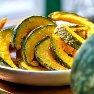 Roasted kabocha squash on a white plate on a wood table.