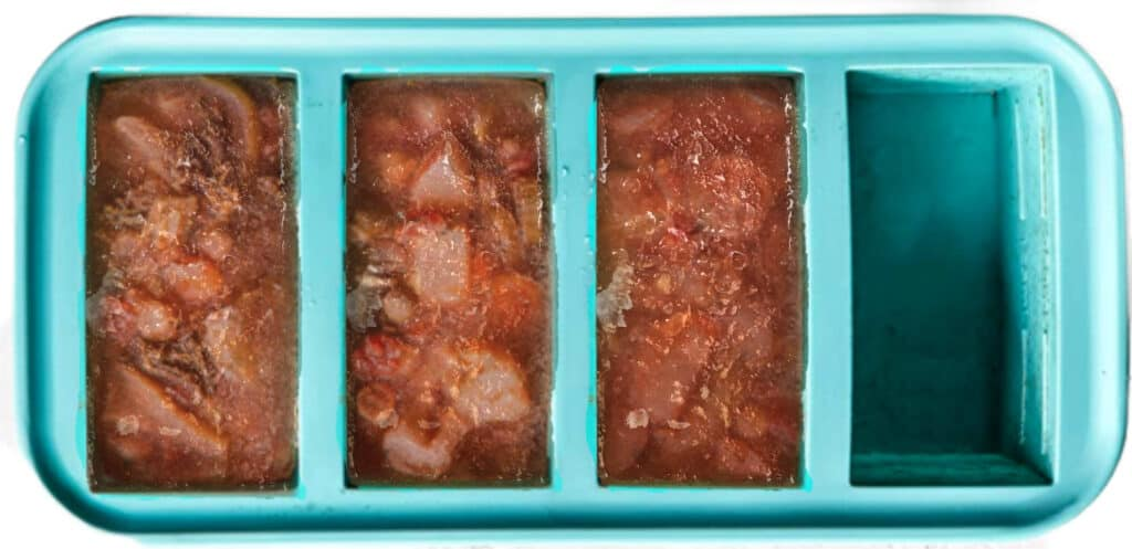 Silicone tray with 3 out of the 4 sections filled with red stew.