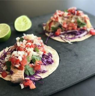 Two tacos on a cutting board.