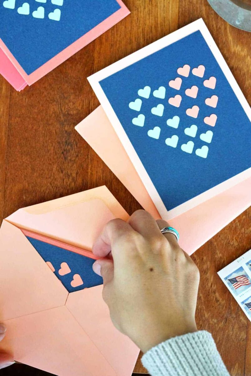 Putting cards with hearts into envelopes.