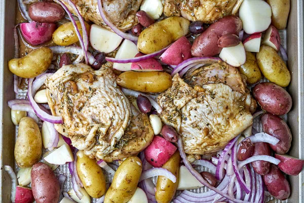 Raw chicken on a baking sheet with potatoes.