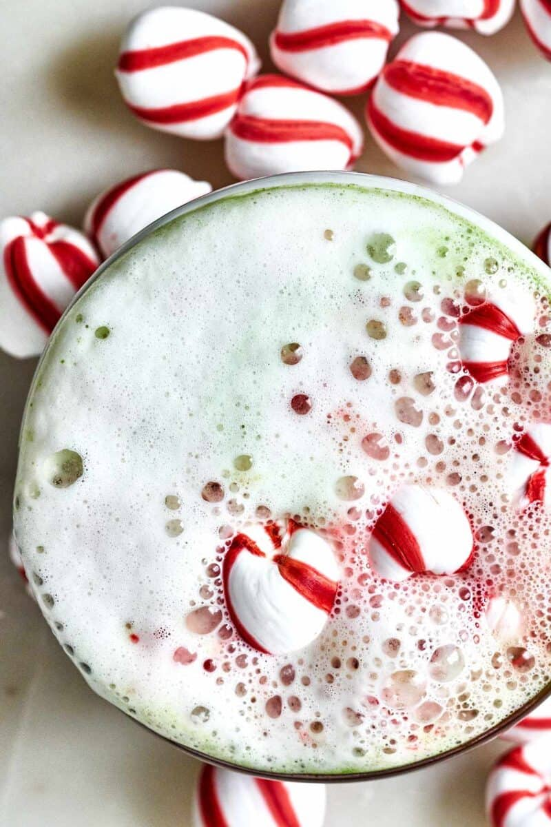 Green and red latte with candy cane candies.