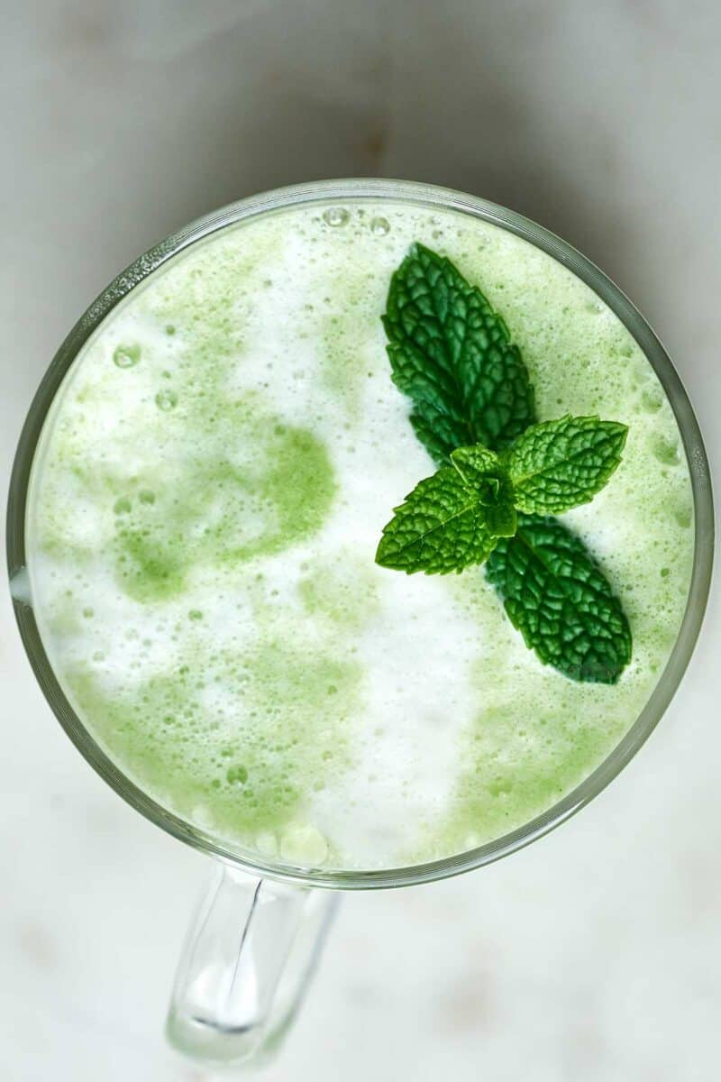 Green latte with a fresh herbs on top.